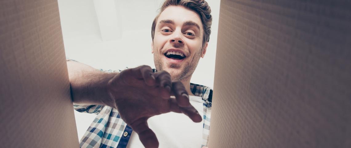 Homme vue contre-plongée en train d'ouvrir un colis en carton.