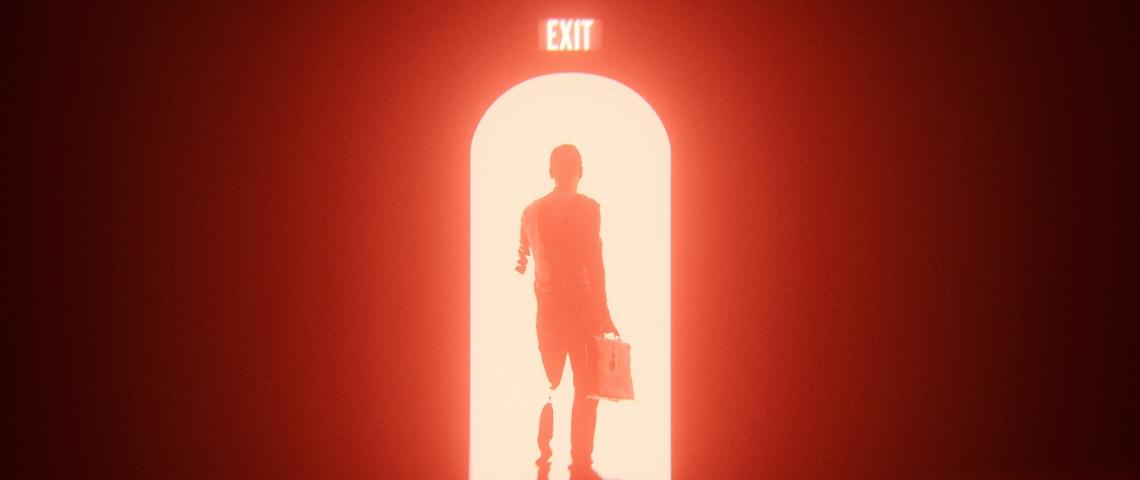 un homme qui passe une porte avec une couleur rouge et un panneau exit au-dessus.