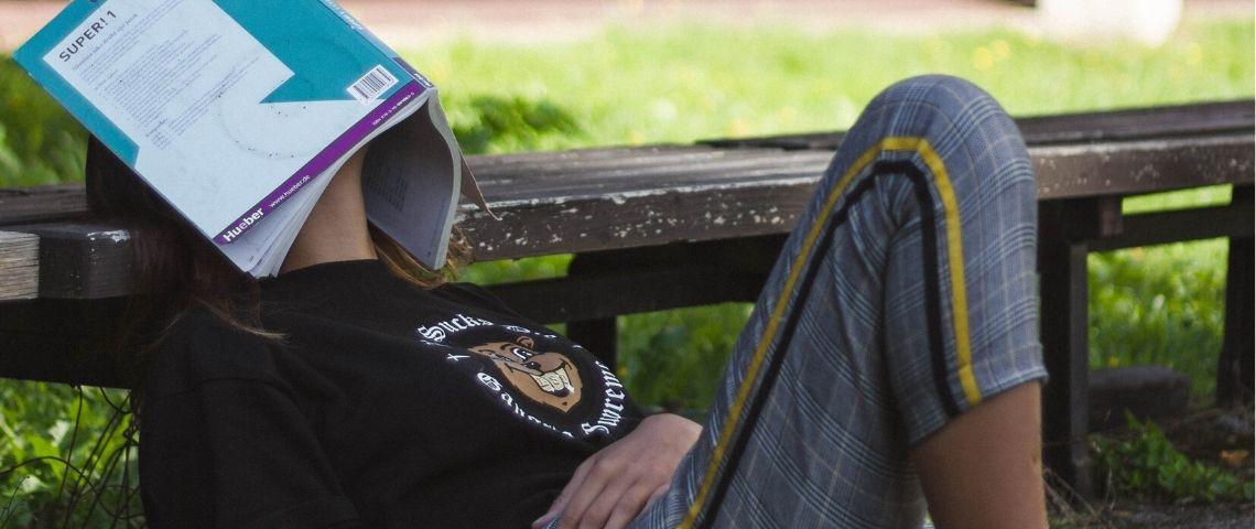 Une jeune femme assise en train de dormir avec un livre sur la tête