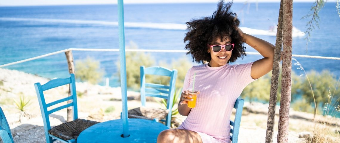 Une femme seule et heureuse qui boit un jus d'orange