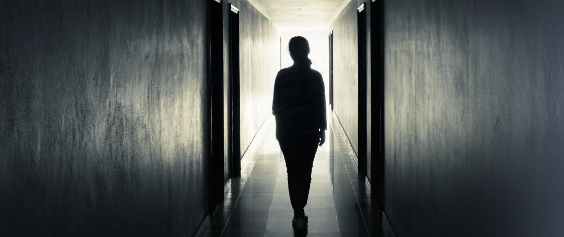 uune femme de dos dans un couloir sombre