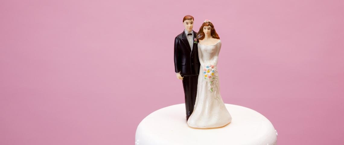 Deux figurines de mariés sur un gâteau de mariage.