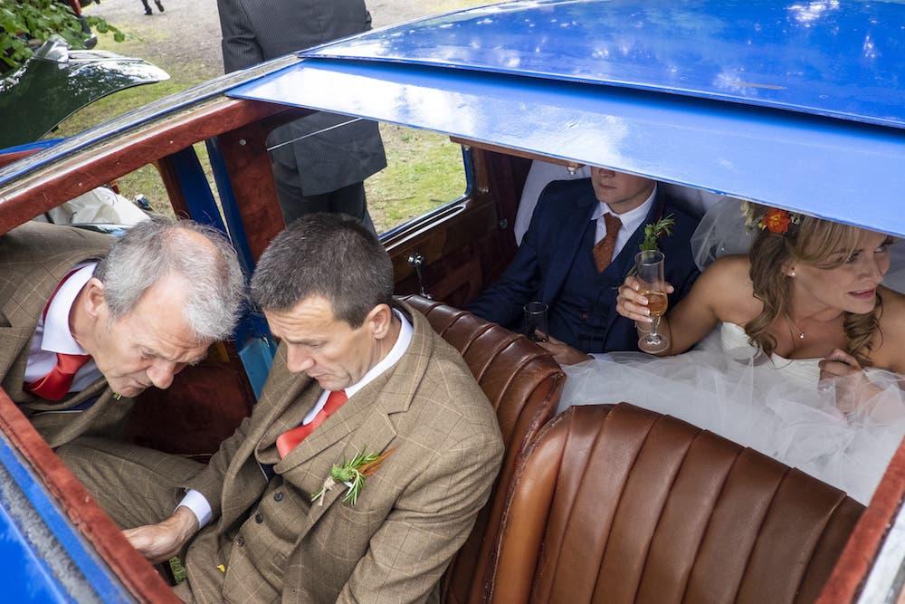 des mariés dans une voiture décapotable