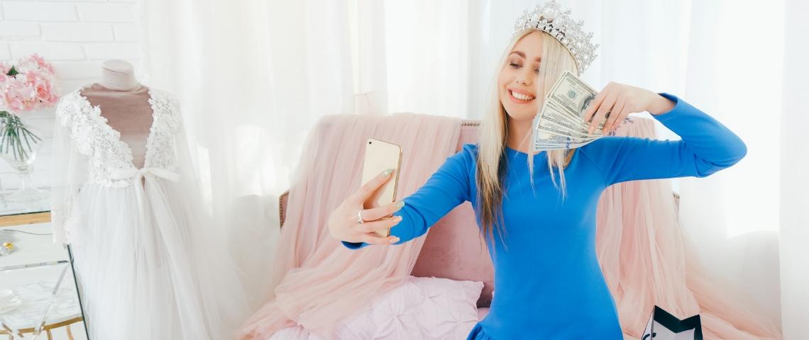 une jeune fille blonde avec une couronne sur la tête se prend en photo avec une liasse de billets dans la main.
