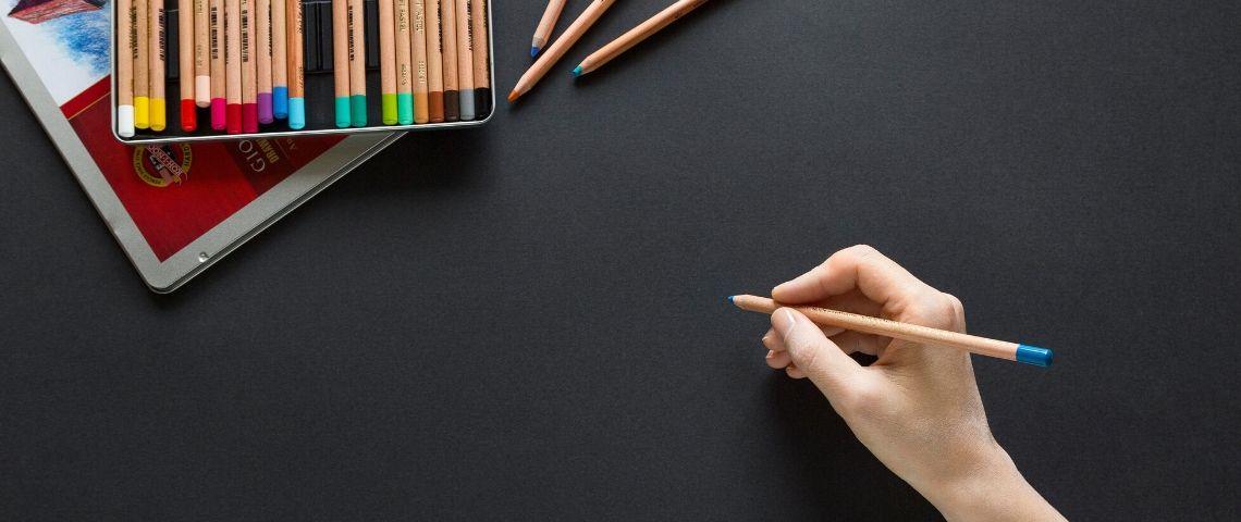 une main avec un crayon de couleur