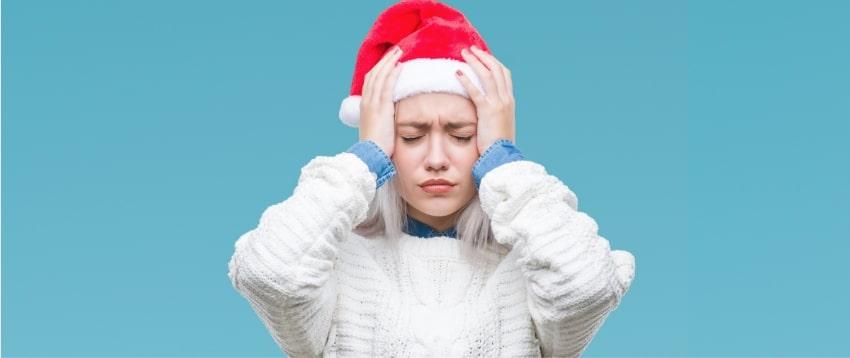 Une jeune femme avec un bonnet de père Noël qui a la migraine