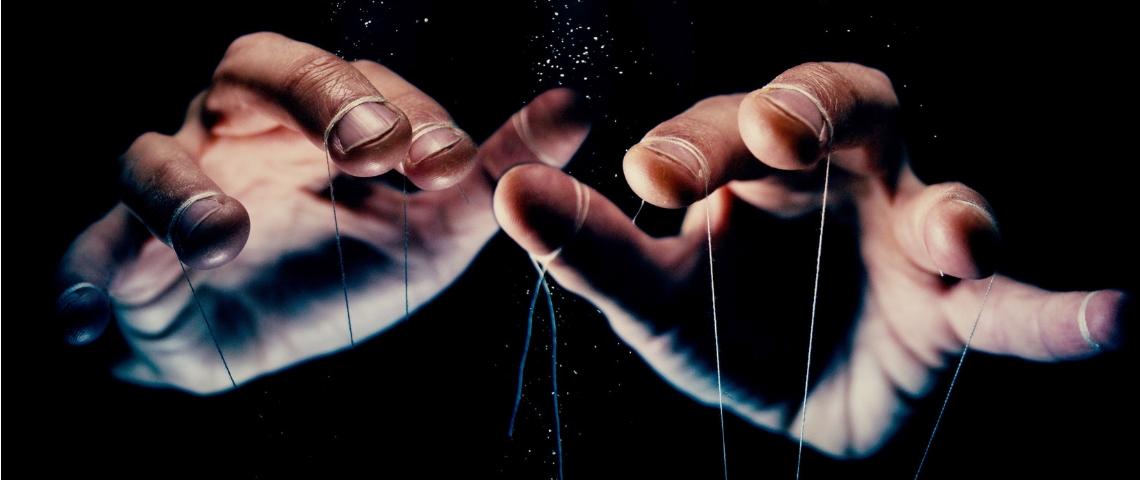 Des mains d'hommes en train de manipuler des ficelles de pantin
