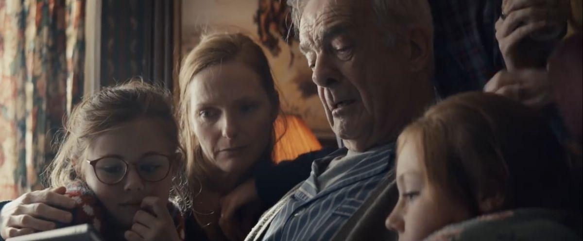Capture de la publicité d'Apple ppur Noël, avec une famille réunit en trai nde regarder un diaporama sur l'Ipad