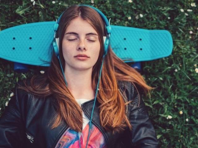 Une jeune femme qui écoutent de la musique avec un casque bleu sur les oreilles