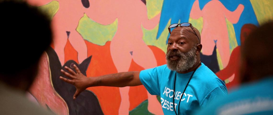 un homme décrit une oeuvre dans un musée