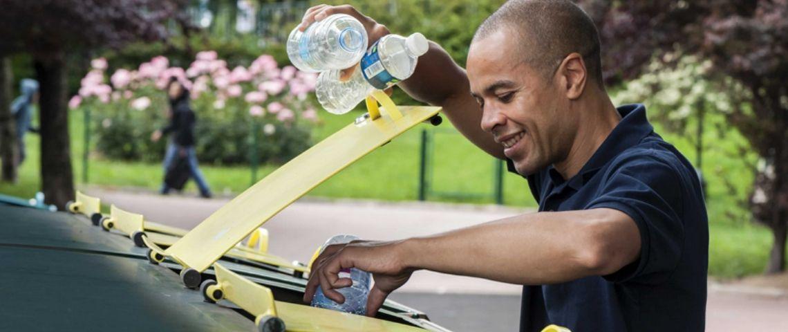 Homme jetant des bouteilles plastiques dans une poubelle dédiée au recyclage