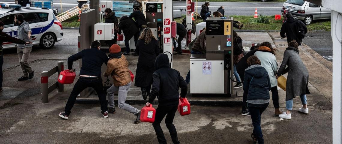 des personnes courent avec des bidons d'essence