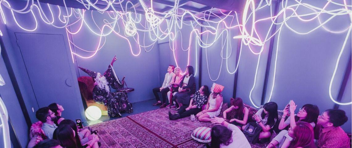 Des gens assis dans une salle avec des néons au plafond