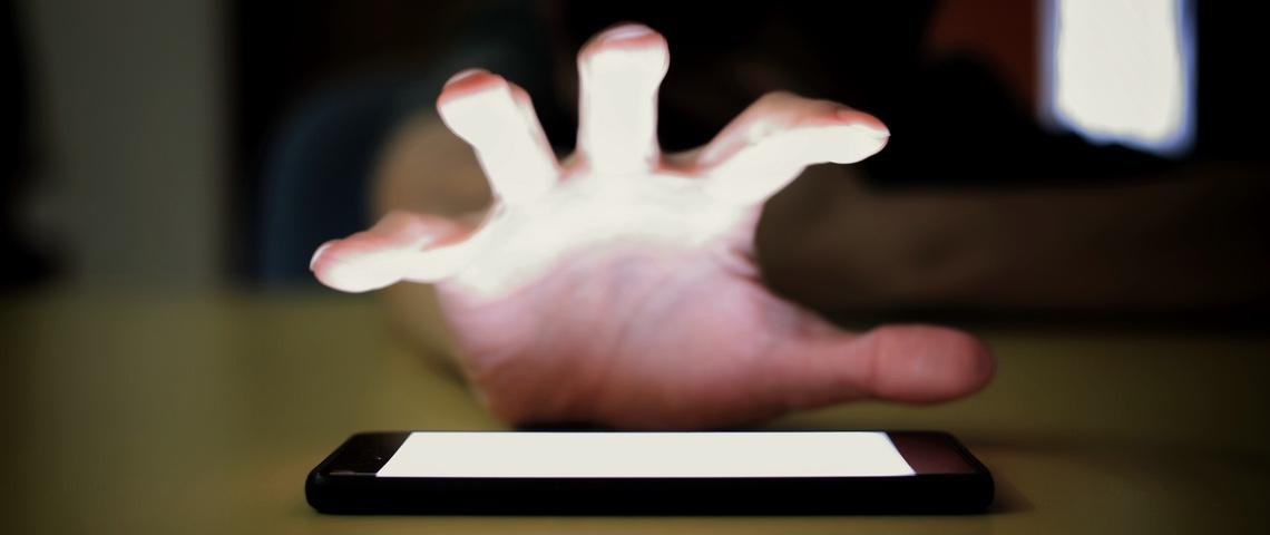 Une main cherche à s'emparer de son smartphone