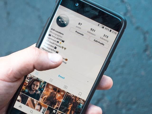 Personne tenant un smartphone danas sa main et navigue sur l'application Instagram