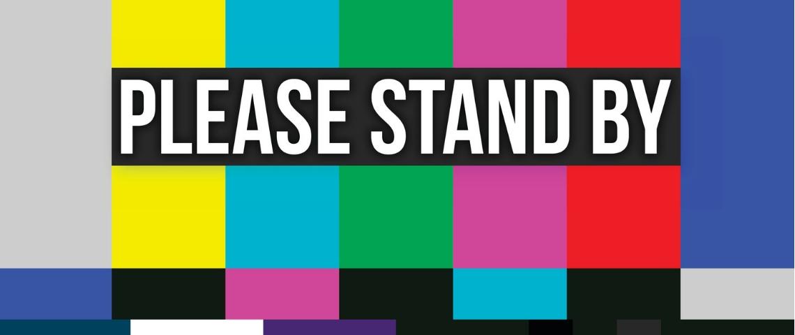 une page d'attente de la télévision avec écris Please Stand By