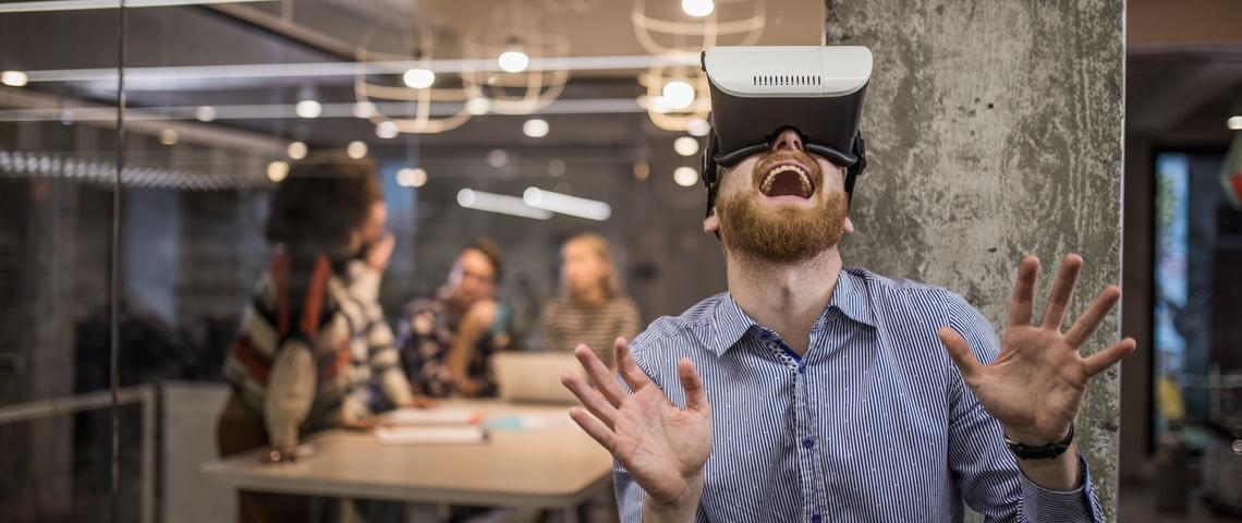 Salarié d'une start-up portant un casque de réalité virtuelle avec un air ébahi