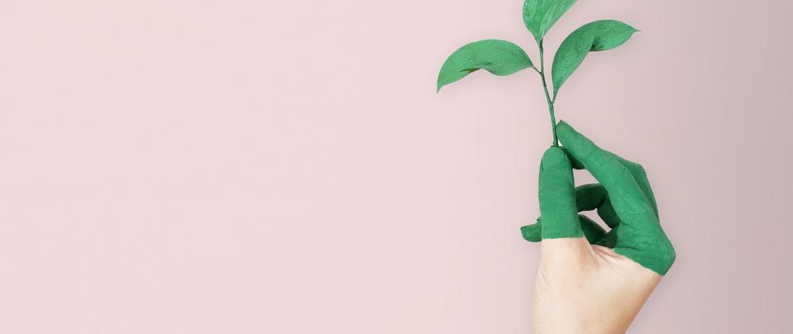 Une main avec de la peinture verte sur un fond rose