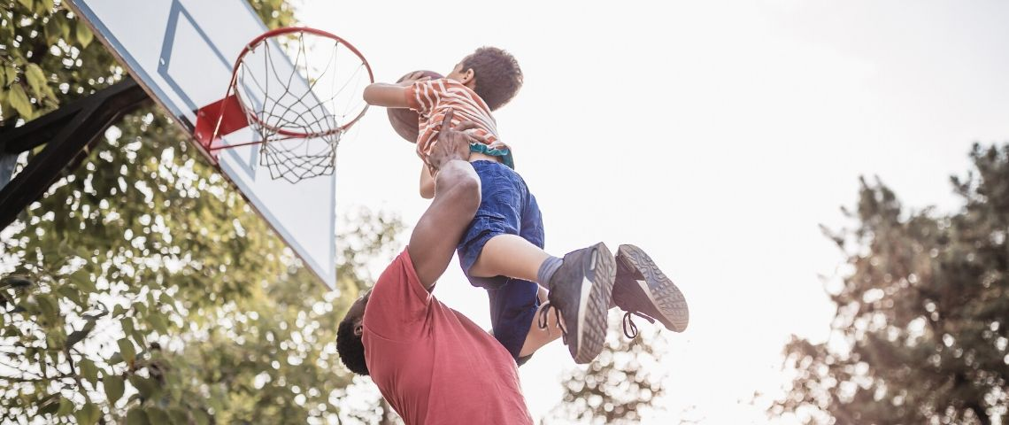 Papa porte son petit garçon qui joue au basket