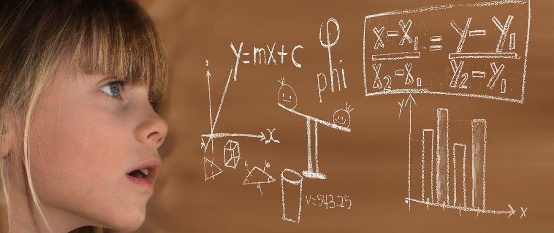 Petite fille regardant de manière dubitative une équation sur un tableau