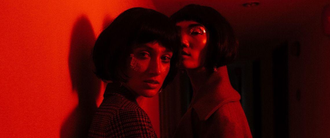 Deux influenceuses se font prendre en photos dans une lumière rouge