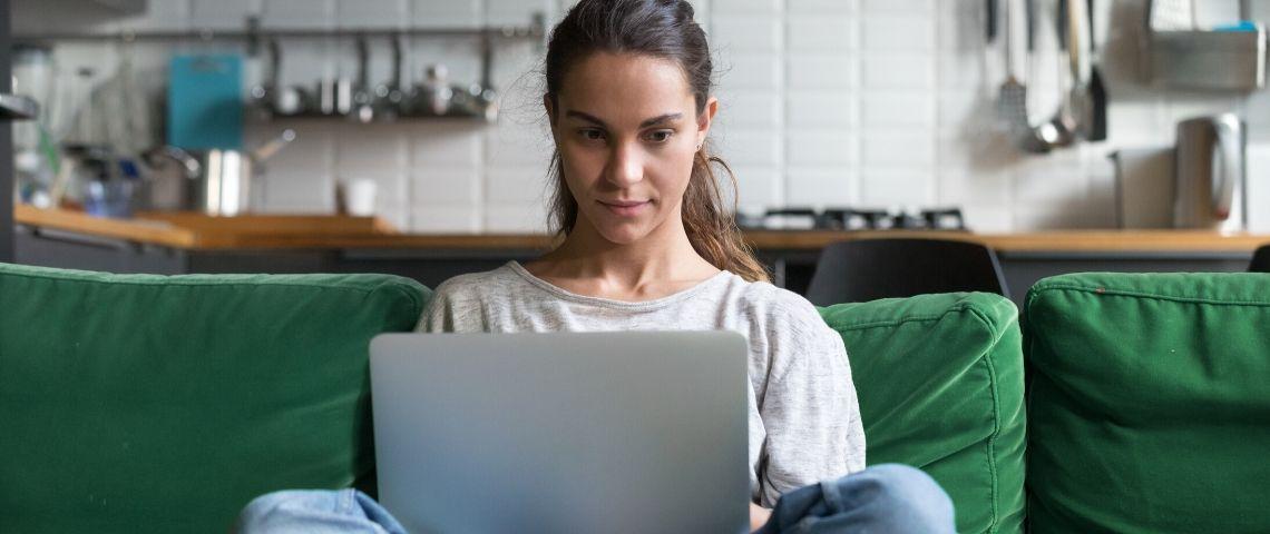 Une femme qui regarde son écran d'ordinateur assise sur son canapé
