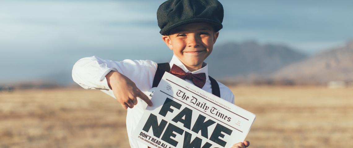 un enfant dans un champs qui tient un journal avec écrit fake news dessus