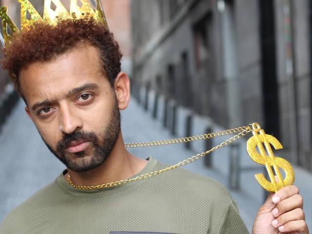 un influenceur dans la rue avec une couronne dorée qui exhibe fiérement un pendantif en forme de dollars