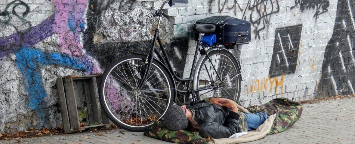SDF dormant au sol, à côté de son vélo