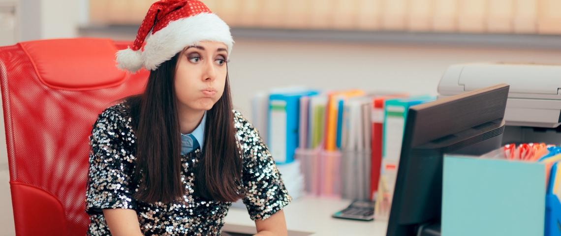Une femme assise à son bureau, portant un bonnet de père noël, en train de s'étirer