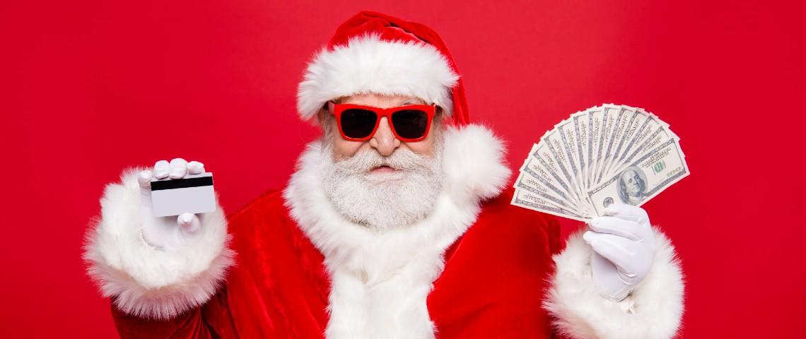 Homme déguisé en père Noël tient une carte bancaire et de l'argent.