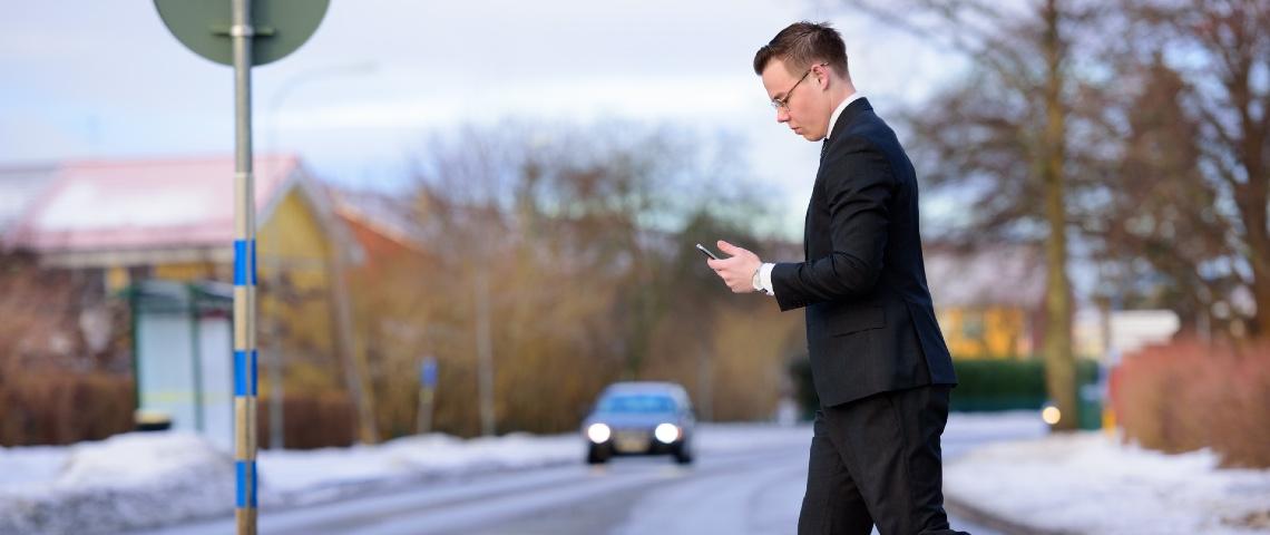 Homme traversant la route en regardant son smartphone