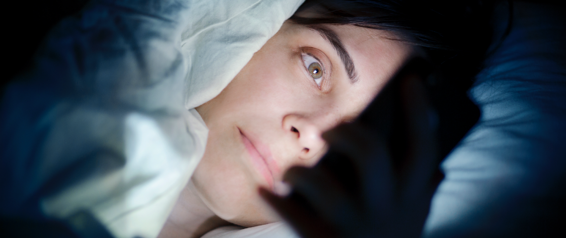 Une femme regarde son smartphone dans son lit