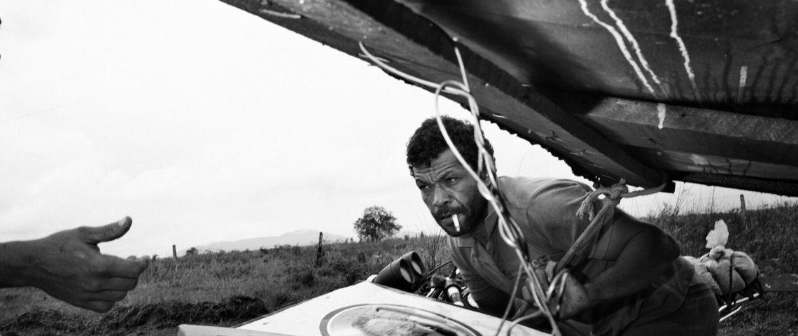 photo noir et blanc d'un homme poussant une charge