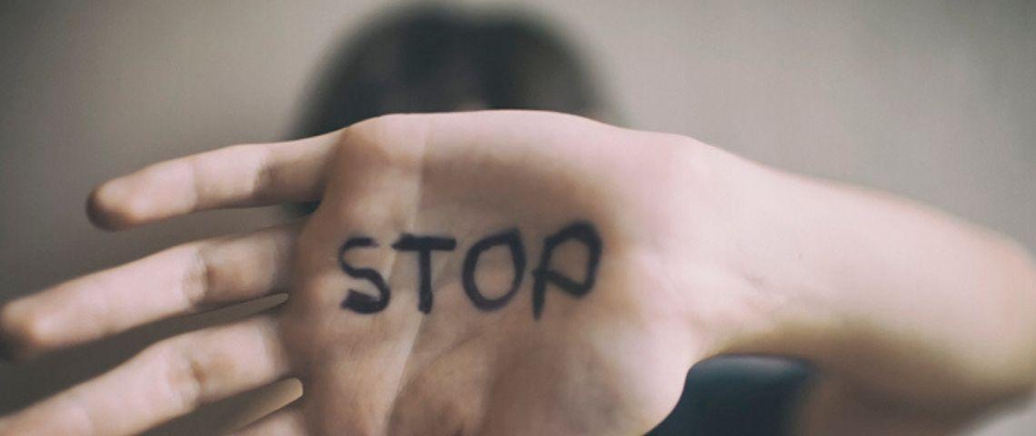 un enfant montre la paume de sa main où est écrit en noir le mot stop