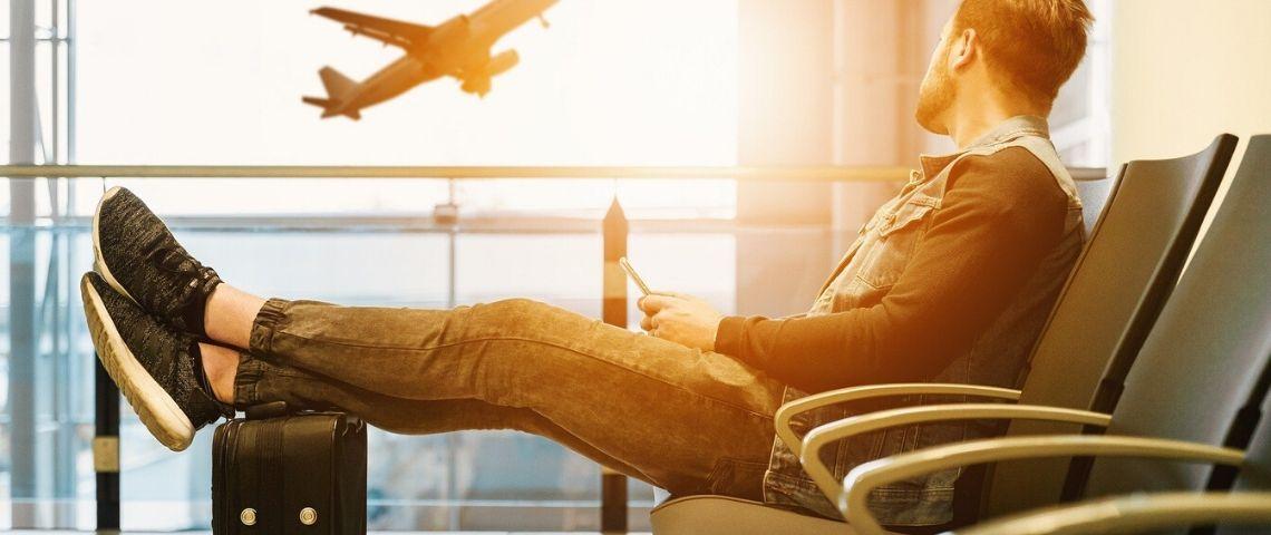Homme regardant un avion s'envolé assis dans un hall d'aéroport