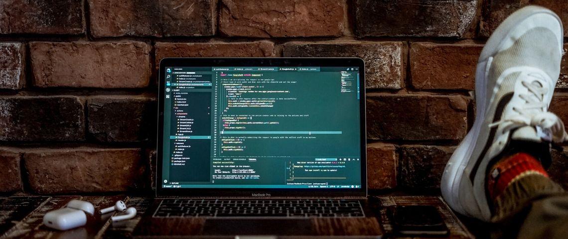 Un ordinateur posé sur un bureau et ouvert sur des lignes de code.