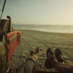 Deux personnes allongées dans un van sur une plage