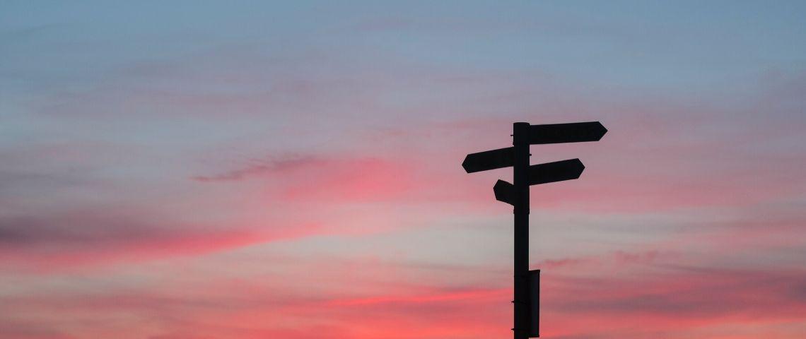 Des panneaux directionnels sur fond de ciel rosé