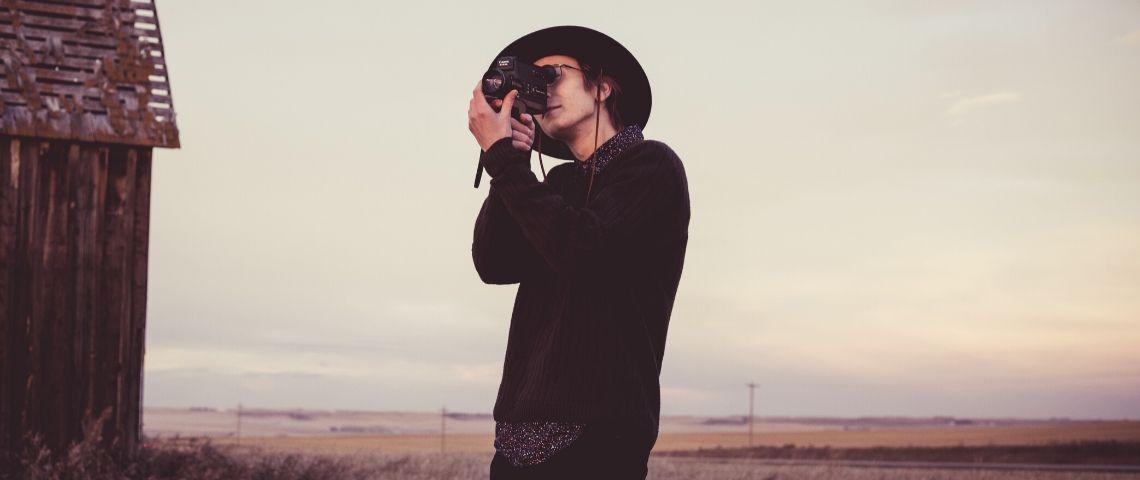 Un homme filme avec une caméra dans les mains