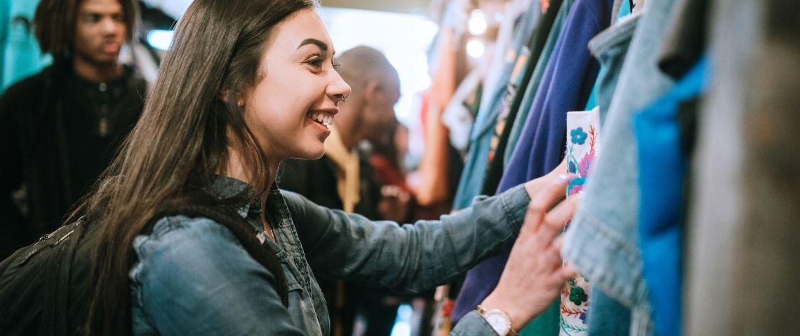 Une jeune femme achète des vêtements dans une friperie
