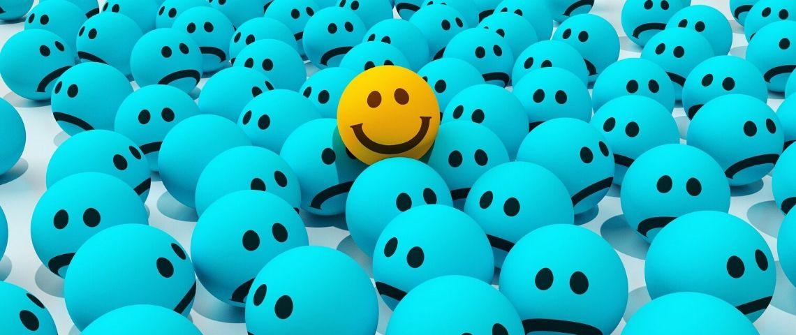 Emojis tristes avec un emojis souriant qui se distingue du lot