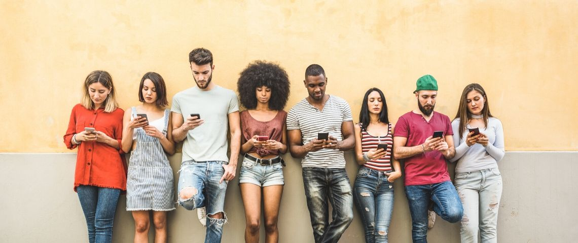 Un groupe de jeunes adossés à un mur jaune consultent leur smartphone.