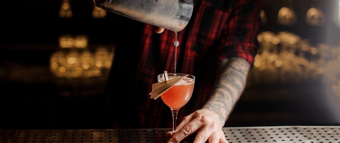 Un barman qui verse un cocktail dans un verre