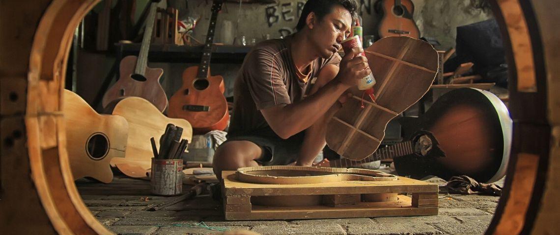 Jeune artisant fabricant une guitare