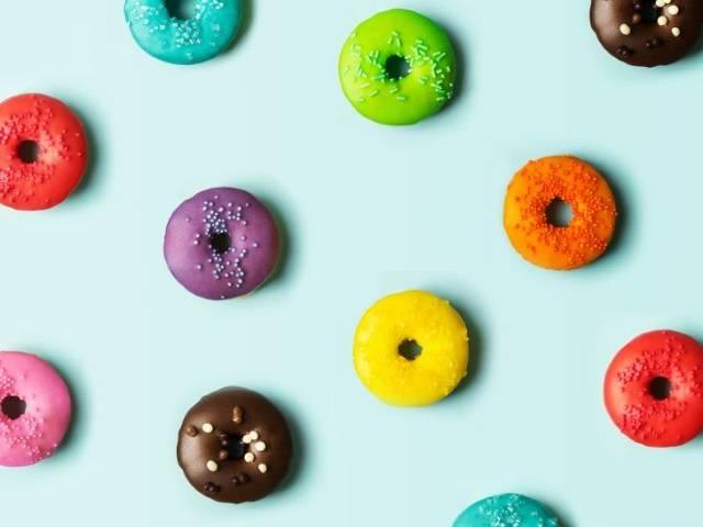 Des donuts de toutes les couleurs sur fond bleu
