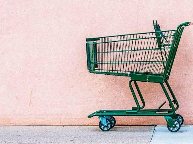 Un chariot de supermarché vert abandonné devant un mur rose