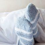 Une paire de pieds avec des chaussettes dans un lit