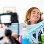 une jeune fille joue avec du slime face caméra.