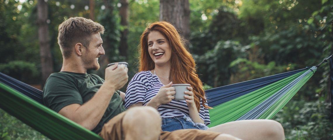 Un couple dans la forêt en train de prendre un café sur un hamac
